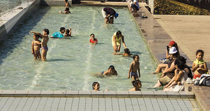 Дети купаются на фонтанах на площади Ала-Тоо в Бишкеке в аномально жаркий день