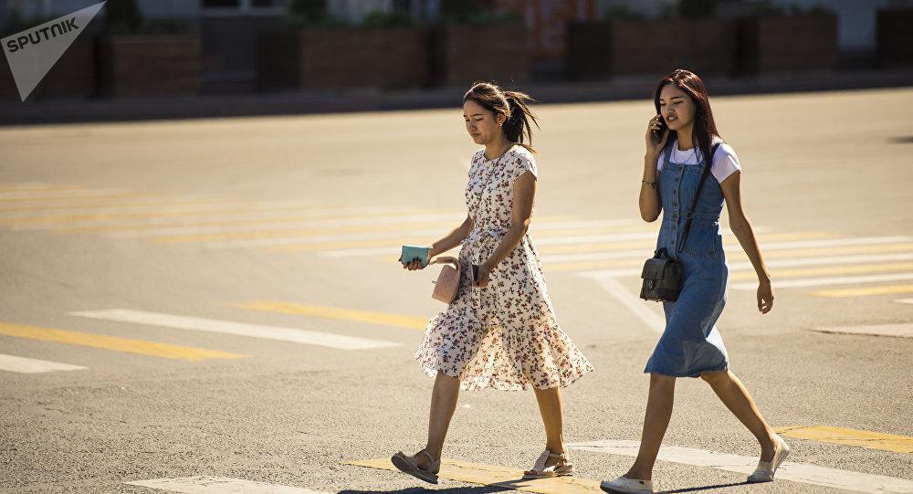 Молодые девушки идут по одной из улиц Бишкека в аномально жаркий день