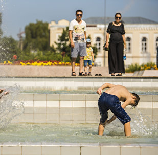 Молодые люди у фонтанов на площади Ала-Тоо в Бишкеке в аномально жаркий день. Архивное фото
