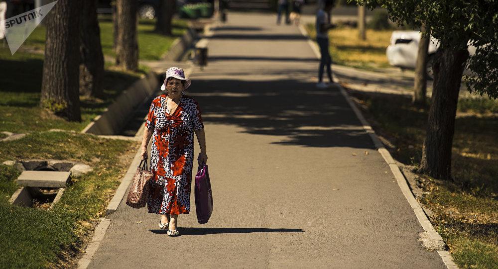 Пожилая женщина с сумками идет по одной из улиц Бишкека в аномально жаркий день