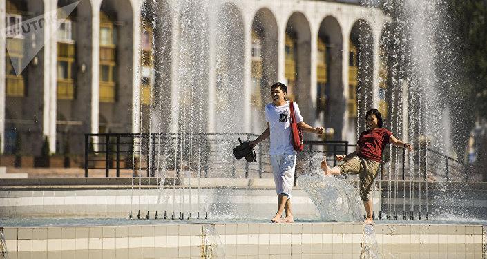 Молодые люди у фонтанов на площади Ала-Тоо в Бишкеке в аномально жаркий день