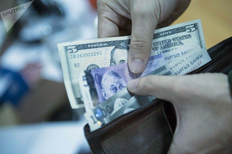 Мужчина вытаскивает долларовую и сомовые купюры из портмоне. Архивное фото