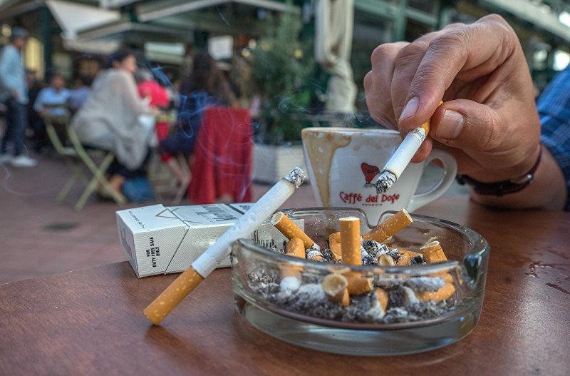 Посетитель одного из ресторанов в Вене курит сигарету. Архивное фото