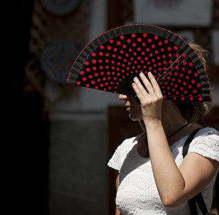 Девушка веером укрывается от солнца. Архивное фото