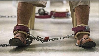 Человек прикован к стулу цепями. Архивное фото