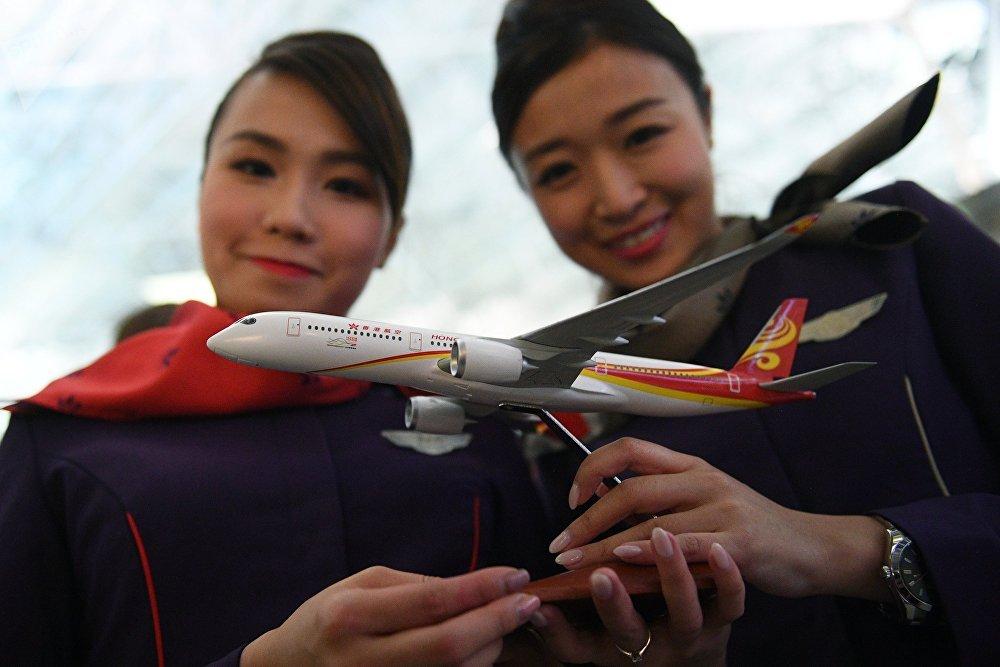 Стюардессы Гонконгских авиалиний позируют с макетом лайнера