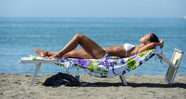 Девушка загорает на пляже. Архивное фото