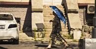 Пожилая женщина с зонтом идет по одной из улиц Бишкека. Архивное фото