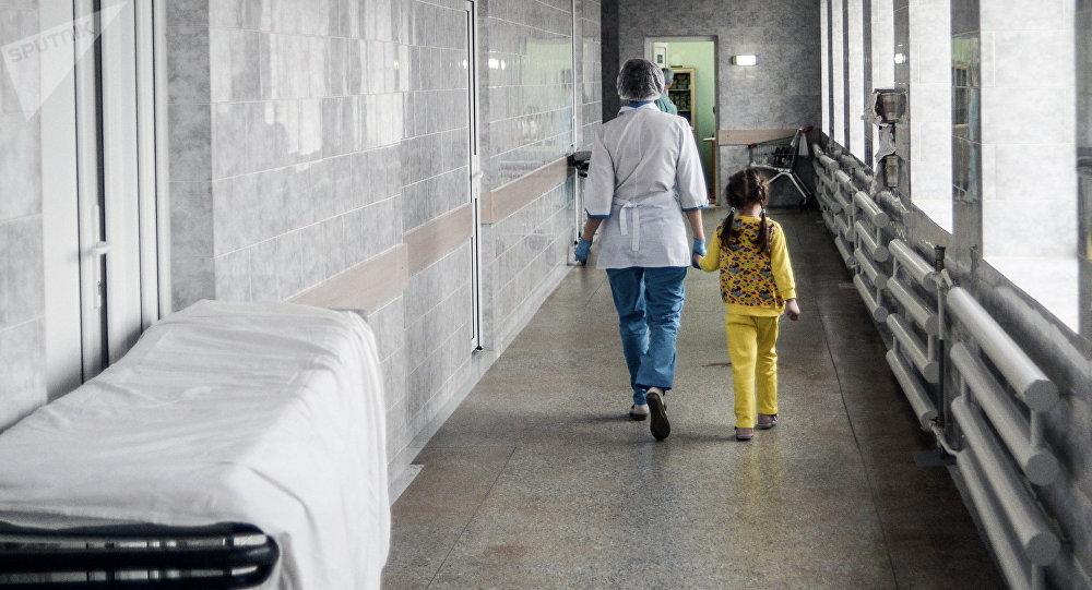 Медсестра с ребенком идут по коридору больницы. Архивное фото
