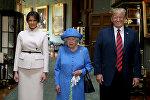 Британская королева Елизавета с президентом США Дональдом Трампом и его женой Меланией в Большом коридоре во время их визита в Виндзорский замок. Великобритания, 13 июля 2018 года