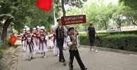 Бишкекте 600 бала жөө жүрүшкө чыгып, Айтматовдун эстелигине гүл коюшту. Видео