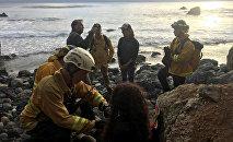 Спасатели оказывают помощь Анджеле Эрнандес, упавшей со скалы за рулем внедорожника в Калифорнии. 13 июля 2018 года
