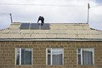 Мужчина проверяет солнечные батареи на крыше дома в деревне. Архивное фото