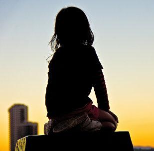 Девочка сидит на крыше дома. Архивное фото