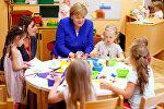 Германиянын канцлери Ангела Меркель Кёльн шаарындагы бала бакчага барып, балдар менен сүйлөшүп отурганда түшкөн сүрөтү