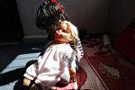 Девочка сидит с куклой. Архивное фото