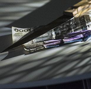 Нож и сомовые купюры на столе. Архивное фото