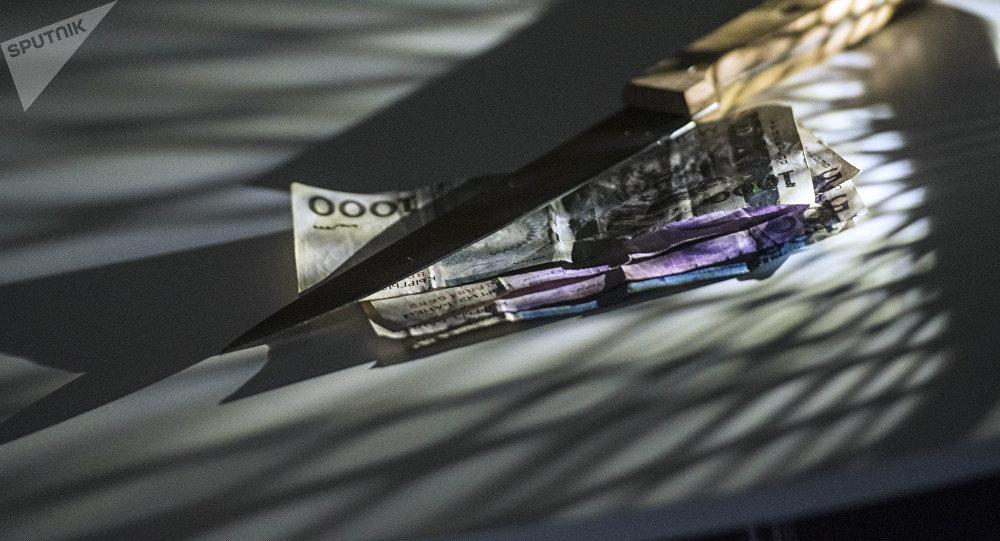 Нож и сомовы купюры на столе. Архивное фото