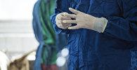 Врач в медицинском халате и перчатках во время работы. Архивное фото