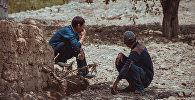 Мужчины сидят у забора в одном из сел Баткенской области. Архивное фото