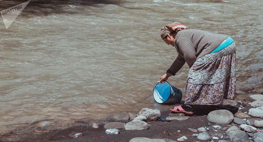 Женщина набирает воду из реки. Архивное фото