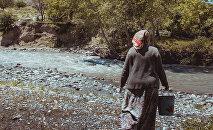 Женщина с ведром у реки в одном из сел Кыргызстана. Архивное фото