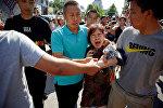 Женщина задержанная сотрудниками службы безопасности у посольства США в Пекине, Китай, 26 июля 2018 года