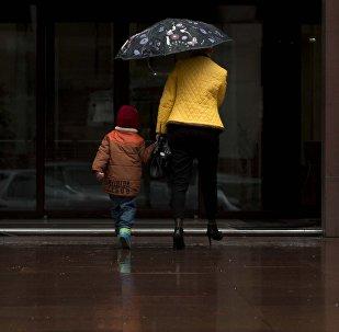 Женщина с ребенком заходят в здание в Бишкеке. Архивное фото