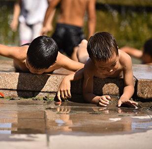 Дети купаются на фонтане в жаркий день в Бишкеке. Архивное фото