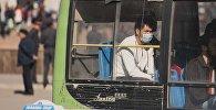 Медициналык маскачан киши автобуста отурат. Архив