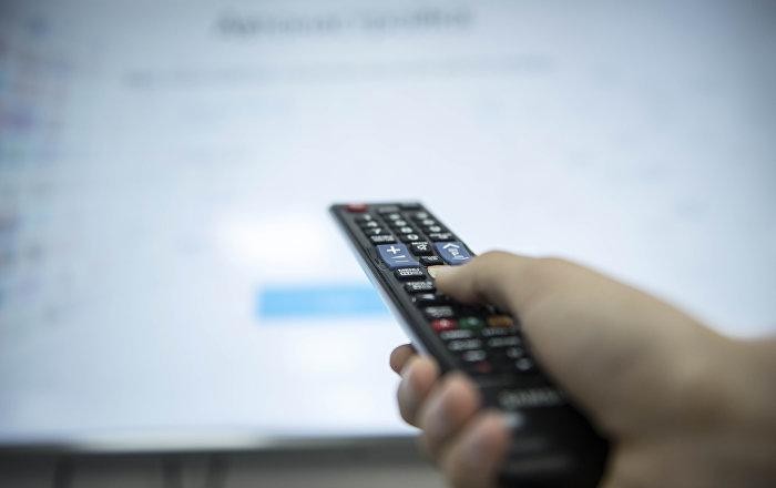 Мужчина держит пульт от телевизора. Архивное фото