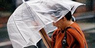 Женщина во время сильного ветра с зонтом в руках. Архивное фото