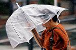 Женщина с зонтом во время сильного дождя и ветра. Архивное фото