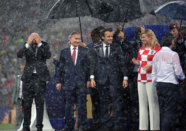 Президент РФ Владимир Путин на церемонии награждения победителей чемпионата мира по футболу FIFA 2018 года на стадионе Лужники. Слева - президент ФИФА Джанни Инфантино, справа налево: президент Хорватии Колинда Грабар-Китарович и президент Франции Эммануэль Макрон.