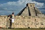 Женщина сидит на плече у мужчины и фотографирует пирамиду Чичен-Ица. Архивное фото