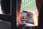 Водитель бишкекской маршрутки едет и смотрит ролик в телефоне. Видео