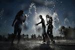 Молодые люди у городских фонтанов в жаркую погоду. Архивное фото
