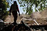 Житель деревни стоит возле рухнувшего дома в районе Каянган после землетрясения в Северной Ломбоке. Индонезия, Архивное фото