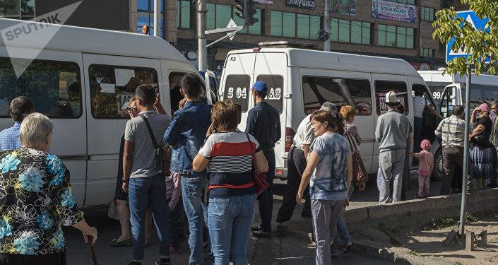 Люди ждут общественный транспорт на остановке в Бишкеке. Архивное фото