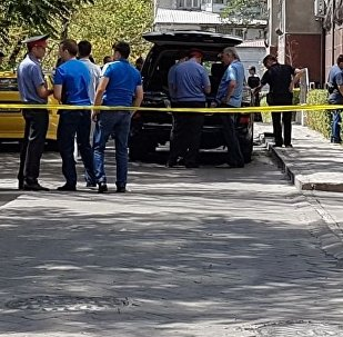 Сотрудники милиции осматривают багажникна месте покушения на бизнесмена. Архивное фото