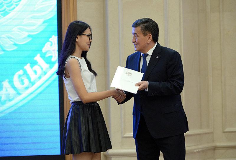 Выпускница Айбийке Омурова во время вручения золотых сертификатов президентом Сооронбаев Жээнбековым