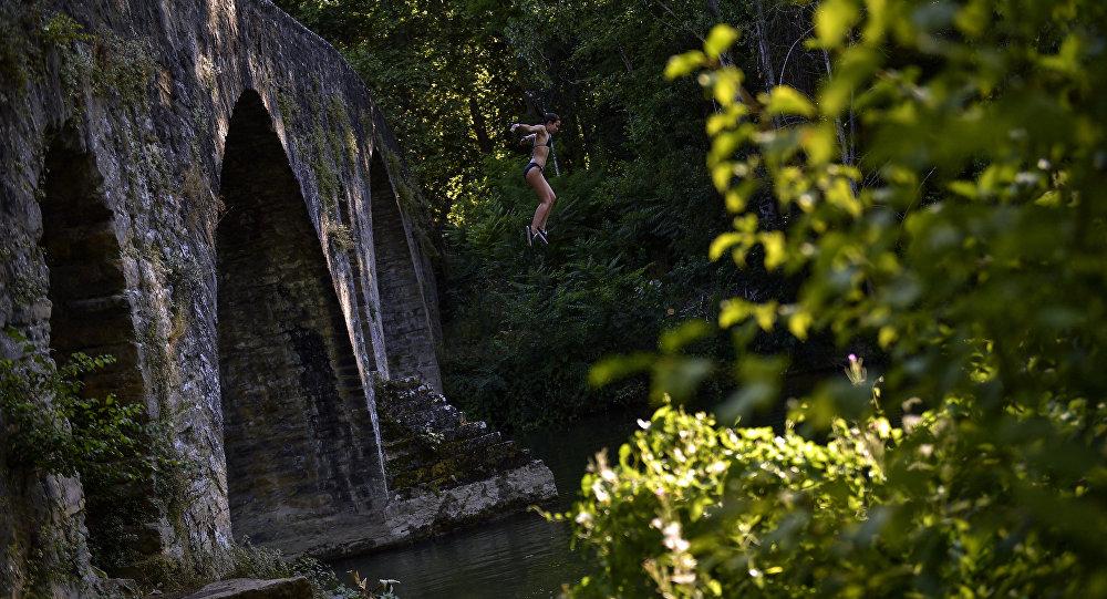 Девушка прыгает с моста в воду. Архивное фото