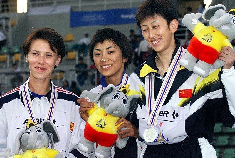 Японская спортсменка Yoko Ota с золотой медалью, китайская легкоатлетка Jin Ling и Анну Чертрова из Кыргызстана с бронзой после вручения медали на легкой атлетике 13-й Азиатской игры на Главном стадионе Спортивный комплекс Университета Таммасат в Бангкоке. 13 декабря, 1998 года