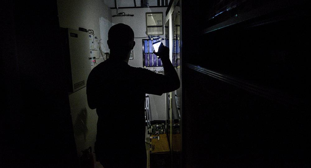 Мужчина с фонариком в руке проверяем электрощит. Архивное фото