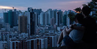 Пара наблюдает за закатом в холме на окраине Гонконга. Архивное фото