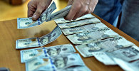 Мужчина ставит на стол долларовые и сомовые купюры. Архивное фото