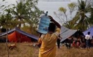 Житель деревни несет галлон питьевой воды после цунами в Ломбоке. Архивное фото