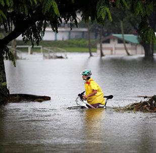 Женщина с велосипедом идет по затопленной улице. Архивное фото