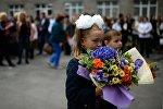 Ученики первых классов с цветами на торжественной линейки посвященной Дню знаний. Архивное фото