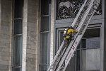 Сотрудник противопожарной службы поднимается по лестнице во время тушения пожара. Архивное фото